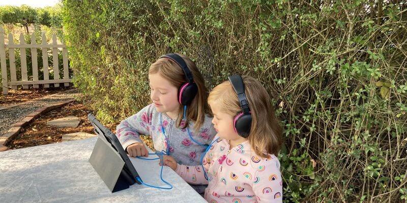 Two girls sharing kids headphones